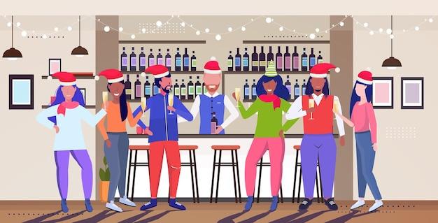 Leute, die weihnachtsfestcafébesucher in den weihnachtsmützen feiern, die spaß weihnachten neujahrswinterferienkonzept modernes restaurantinterieur haben