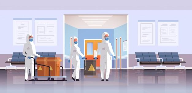 Leute in schützenden hazmat klagen, die fässer mit warnzeichengrippeausbruchporzellan-krankheitserreger-atmungsquarantäne coronavirus konzeptkrankenhausinnenraum horizontal tragen