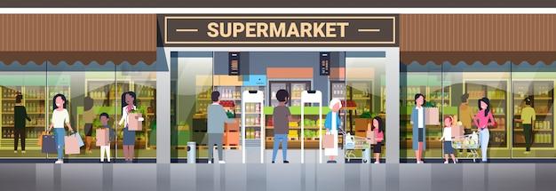 Leutegruppe, welche die taschen drücken die laufkatzen mit dem lebensmitteleinkaufenkonsumismuskonzept hält, moderner lebensmittelgeschäftsupermarkt außen horizontal in voller länge