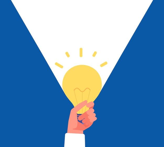 Licht der idee. hand, die glühbirne auf blau und weiß hält