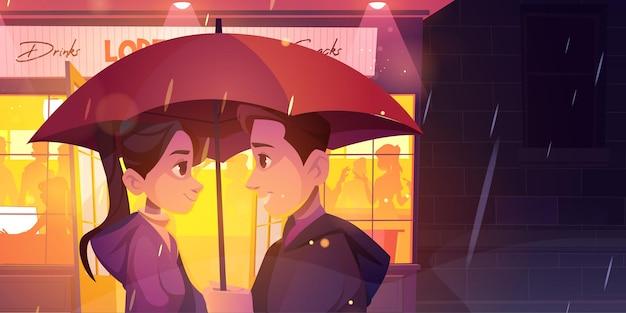 Liebesgeschichtenpaar steht unter regenschirm an regnerischer nachtstraßenfront des glühenden caféfensters romantischer r ...