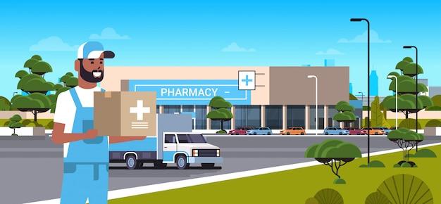Lieferbote, die medizinische produkte in pappkarton mit kreuzzeichen moderne drogerie vorderansicht apotheke ladengebäude außenmedizin gesundheitswesen lieferservice konzept horizontales porträt tragen