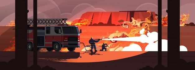 Löschfahrzeug und feuerwehrmänner, die gefährliches verheerendes feuer in kämpfendem trockenem holz des buschfeuers australiens brennen die bäume, die die intensiven orange horizontalen flammen des naturkatastrophenkonzeptes feuern
