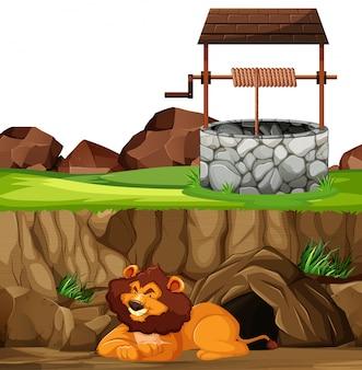 Löwe in der liegenden pose im tierparkkarikaturstil auf höhle und brunnenhintergrund