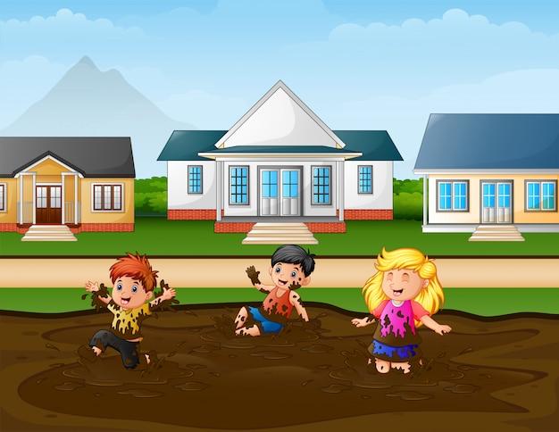 Lustige kinder, die eine schlammpfütze in der ländlichen szene spielen