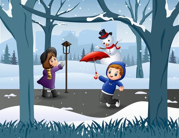 Lustige kinder, die im verschneiten park spielen