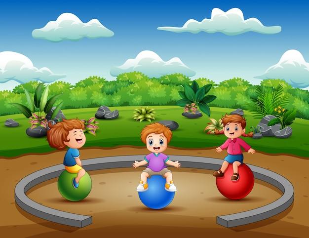 Lustige kleinkinder, die auf der kugel sitzen