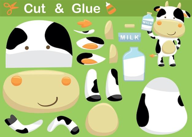 Lustige kuhkarikatur, die beim halten der flaschenmilch steht. bildungspapierspiel für kinder. ausschneiden und kleben
