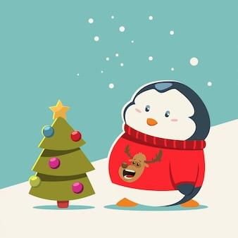 Lustiger babypinguin in einer gestrickten strickjacke mit einem rotwildkopf steht nahe weihnachtsbaum.