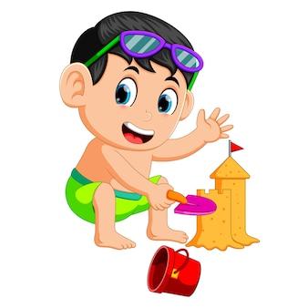 Lustiger junge, der eine große sandburg am strand bildet