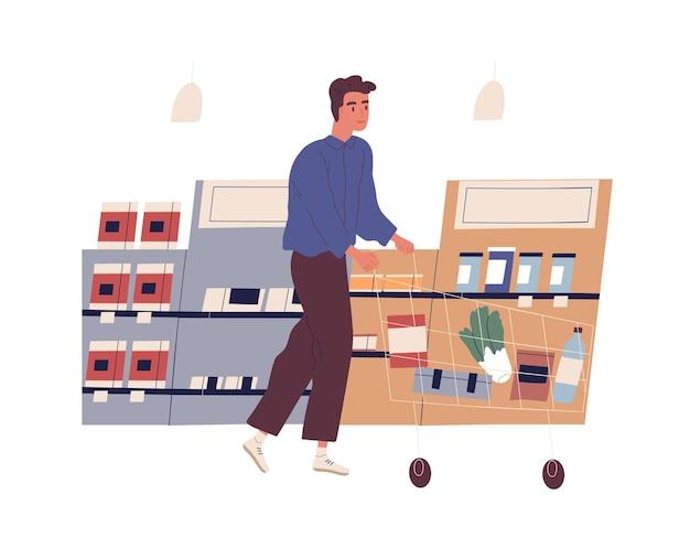 Lustiger junger mann mit einkaufswagen, der lebensmittel am lebensmittelgeschäft kauft. netter junge, der entlang regale mit produkten am supermarkt geht