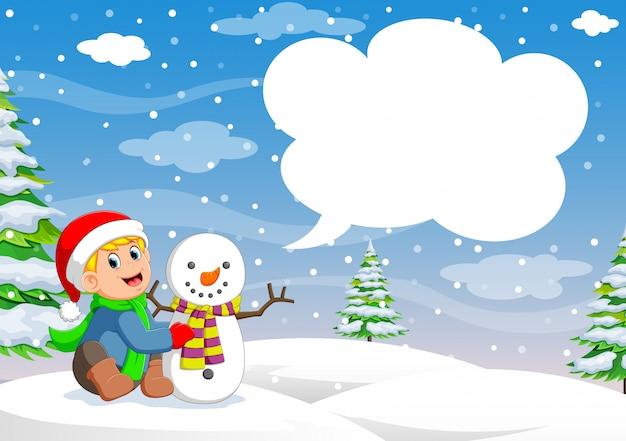 Lustiger kleiner kleinkindjunge in einer roten gestrickten nordischen mütze und in einem warmen mantel, die mit einem schnee spielen