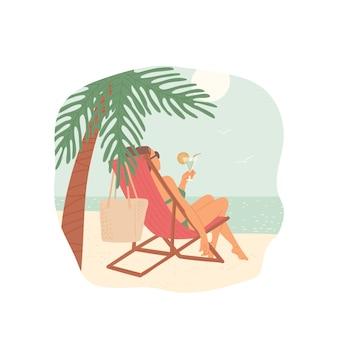 Mädchen am strand sitzt auf chaiselongue unter palme mit cocktail in ihren händen und schaut auf meer