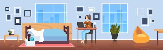 Mädchen blogger kommentieren spielprozess video bewertung bloggen live-streaming-konzept spieler in kopfhörern mit gamepad spielen spiele auf laptop wohnzimmer interieur in voller länge horizontal
