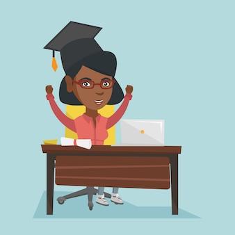 Mädchen, das am tisch mit laptop und diplom sitzt.