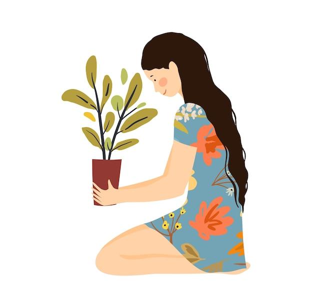 Mädchen, das auf dem boden mit blumentopfpflanze hält, die in den händen hält.