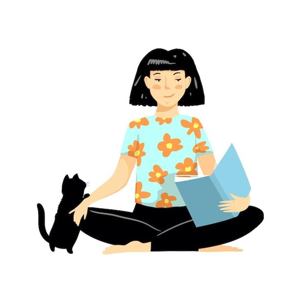 Mädchen, das auf dem boden sitzt und buch liest, das schwarzes niedliches kätzchen streichelt.