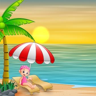 Mädchen, das auf einem ruhesessel unter sonnenschirm am strand sich entspannt
