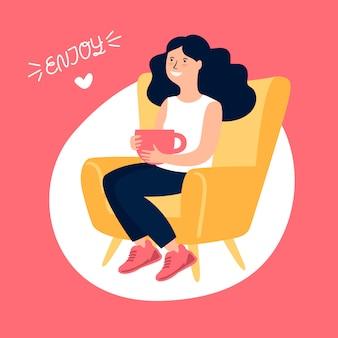 Mädchen, das auf einem stuhl mit tasse tee sitzt