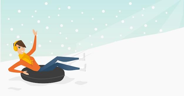 Mädchen, das auf schneegummischlauch in den bergen rodelt
