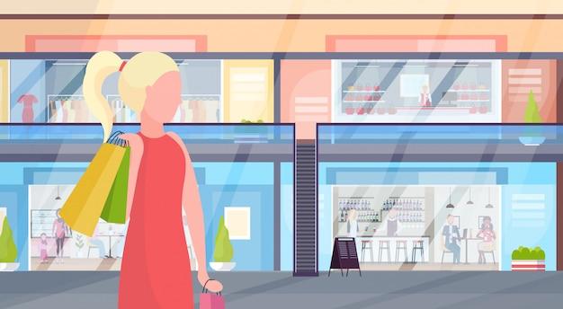Mädchen, das bunte einkaufstaschen große verkaufskonzeptfrau trägt, die modernes einkaufszentrum mit kleidung und cafés supermarktinnenraum horizontale porträtwohnung geht