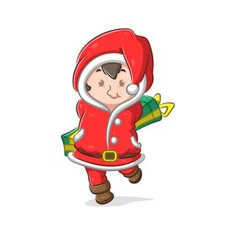 Mädchen, das das weihnachtsmannkostüm benutzt und das lange grüne geschenk hält