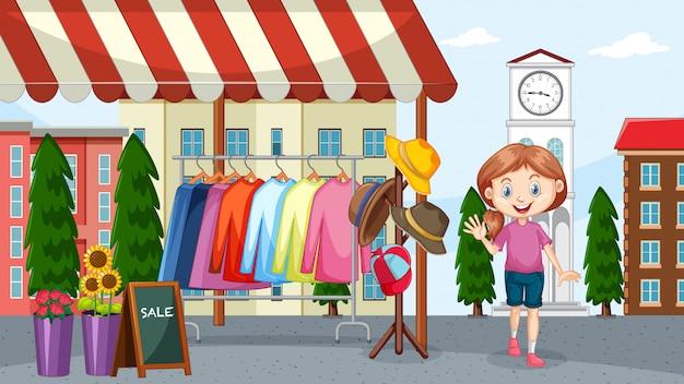 Mädchen, das kleidung am flohmarkt verkauft