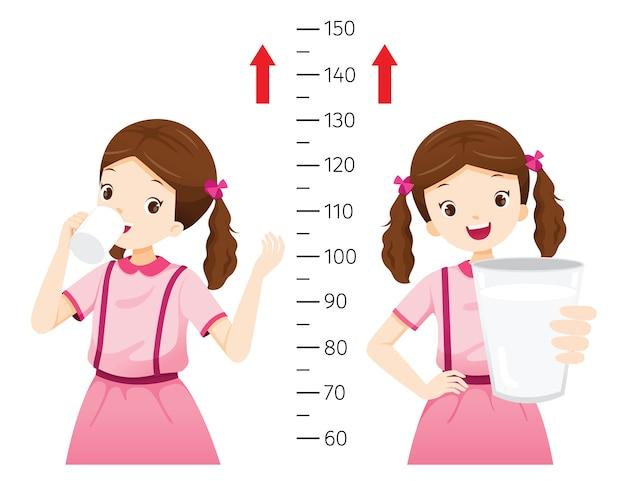 Mädchen, das milch für gesundheit und größer trinkt. mädchen, das ihre größe misst.
