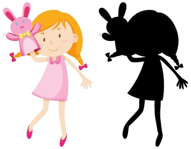 Mädchen, das mit puppenhand in farbe und schattenbild spielt