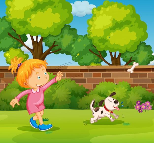 Mädchen, das mit schoßhund im yard spielt
