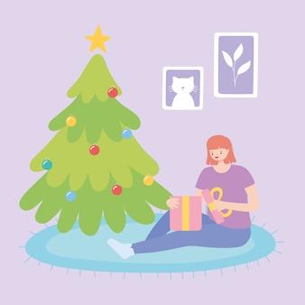Mädchen, das nahe baumweihnachtsfeier öffnet geschenkbox-vektorillustration sitzt