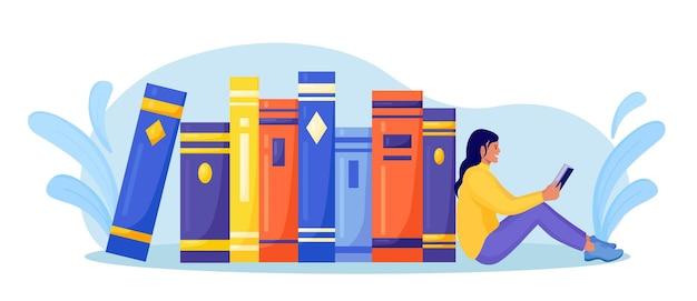 Mädchen, das nahe stapel büchern sitzt und buch liest. online-bibliothek, buchhandlungen, e-book. internet-bildung