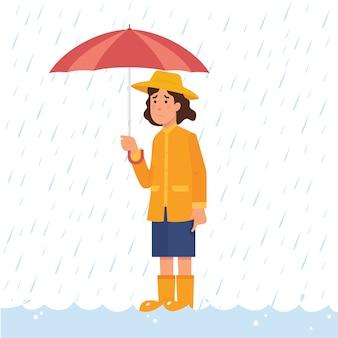 Mädchen, das regenschirm im starken regen und in der flut hält