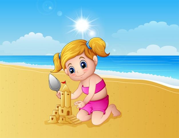 Mädchen, das sandburg am strand bildet
