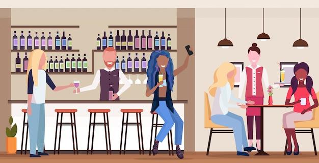 Mädchen, das selfie-foto auf smartphone-kamera-mix-race-leuten macht, die sich in der bar entspannen, die cocktails trinkt barmann und kellnerin, die kunden modernes café-interieur horizontal in voller länge dienen