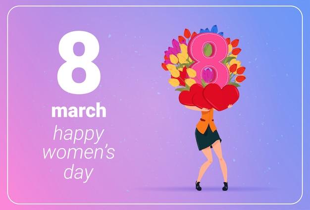 Mädchen, das tulpen-blumen und rot-herz-glückliches frauen-tages8. märz-feiertags-konzept hält
