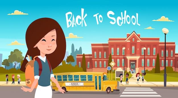 Mädchen, das zurück zu schule über der gruppe schülern geht vom gelben bus
