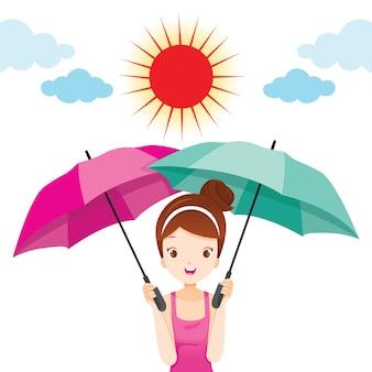 Mädchen, das zwei regenschirme hält, um sonnenlicht zu schützen
