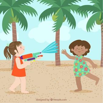 Mädchen, die mit wasserwerfern im strand spielen
