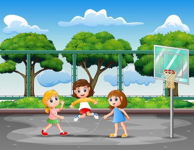 Mädchen, die springseil im basketballplatz spielen