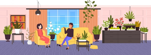 Mädchen diskutieren während des treffens frauen, die im modernen wohnzimmer mit zimmerpflanzen grünes innen entspannen