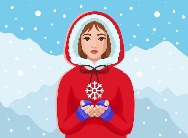 Mädchen in einem roten mantel, der im winter eine schneeflocke in den händen hältkonzept von winter und weihnachten