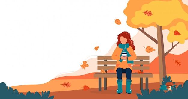 Mädchen mit dem kaffee, der auf bank im herbst sitzt.