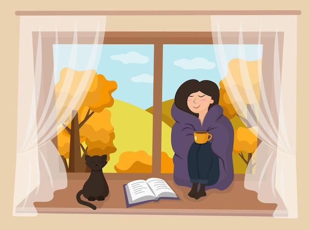 Mädchen mit einer tasse kaffee, liest ein buch im herbstfenster. herbst. die katze steht am fenster.