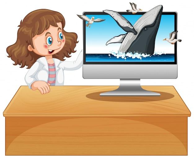 Mädchen neben computer mit buckelwalhintergrund