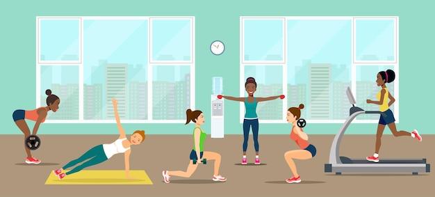 Mädchen nehmen eine hantel und machen cardio im fitnessstudio.