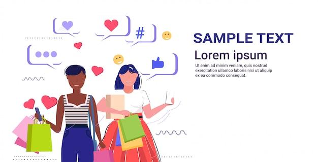 Mädchen paar mit online-mobile-app social-media-netzwerk chat blase kommunikation digitale sucht konzept mix race frauen tragen einkaufstaschen kopie raum skizze porträt horizontal