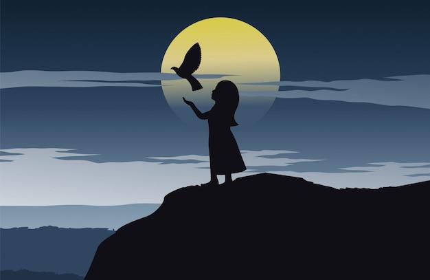 Mädchen setzen vogel in die freiheit, die auf einer klippe stehen