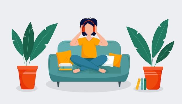 Mädchen sitzt auf dem sofa und hört hörbücher oder musik