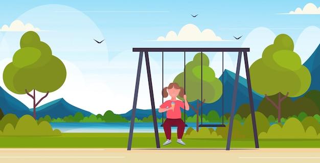 Mädchen sitzt auf schaukel essen eis ungesunde ernährung fettleibigkeit konzept weibliches übergewichtiges kind schwingt spaß im freien sommerpark landschaft flach in voller länge horizontal